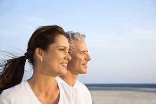 Side view of smiling middle aged couple on beach looking